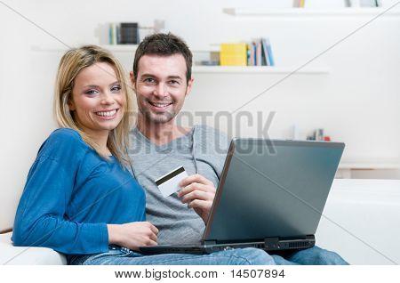 Uśmiechnięta młoda para robiąc zakupy online z kart kredytowych i laptopa w domu