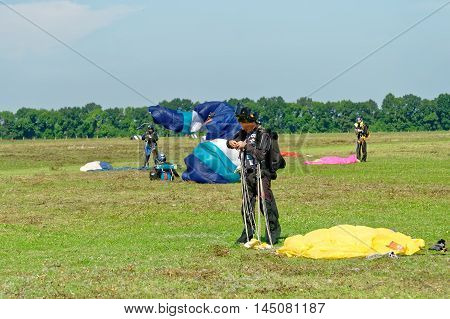 Kharkiv Ukraine - August 20 2016: Skydiver unfasten his parachute after landing at the airfield Korotych Kharkov region Ukraine on August 20 2016