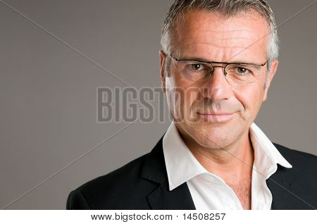 Mature man with pair of glasses looking at camera with satisfaction