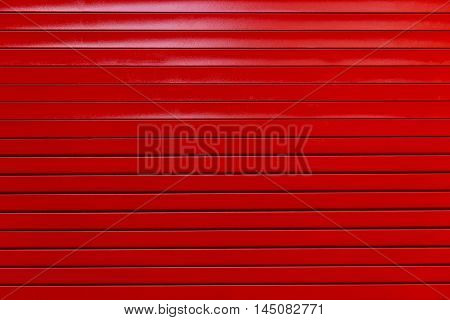 Red painted metal garage door or wall. Red garage door with black stripes. Black and red metal wall background.