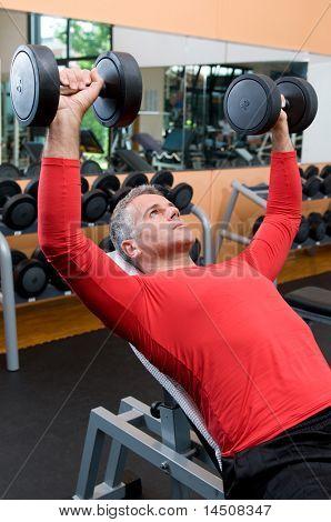 Volwassen man opheffing dumbells tijdens fitness gym