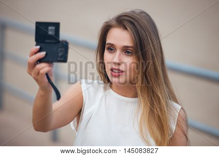 Beautiful girl sitting outdoors and taking selfie video for fashion blog. Woman holding compact camera in her hand ant taking photo.