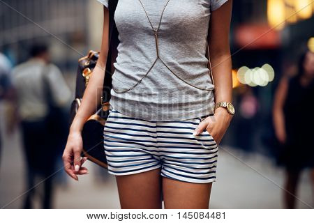Outfit details of fashion elegant stylish woman posing. Female summer outfit with short striped blue and white shorts grey t-shirt modern leather backpack and golden jewelry and watch standing on city street.