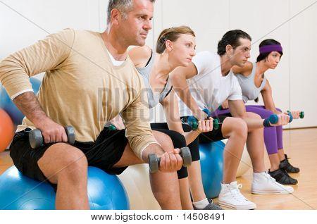 Gesunde junge Menschen heben Hantel und sitzt auf einem Fitness-Ball in Fitnessstudio, Instructor auf Vordergrund