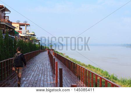 A boy walks along a boardwalk next to Mekong river at a small town named Chiang Khan Thailand.