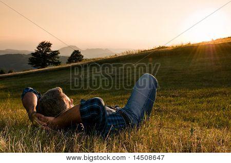 Amadurecer o homem fazer uma pausa e relaxar em um prado na maravilhosa luz quente por do sol
