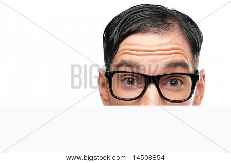 Close up of surprised nerd behind a white sign board isolated on white background