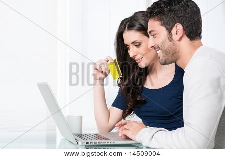 Smiling satisfied couple buying online with credit card at home