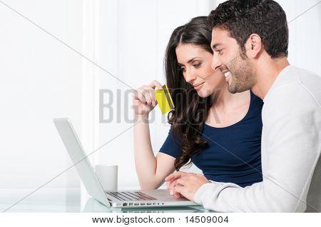 Lächelnd zufrieden paar kaufen online mit Kreditkarte zu Hause