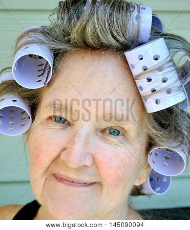Mature female senior expressions wearing hair rollers.