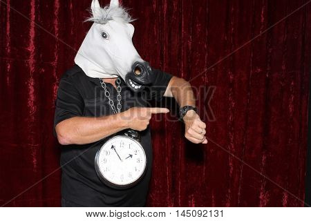 An unidentifiable man wears a rubber Horse Head a Clock around his neck in a Photo Booth.