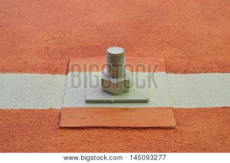 Nut and bolt mounted on colored wall