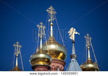 Gilded angel shaped weathervane on the steeple blurred golden domes and crosses and blue sky on background; Chernigovsky Skit Sergiev Posad Russia.