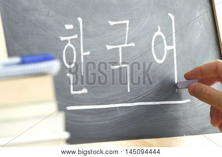Hand writing on a blackboard in a Korean class with the word