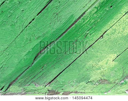 Green chipping paint on diagonal wood planks