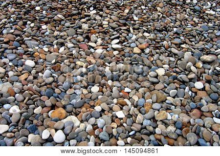 Colorful small stones on Omaha Beach, Normandy France.