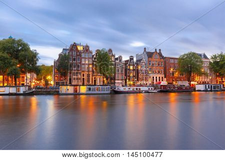 Amsterdam canal Amstel with typical dutch houses and boats during twilight blue hour, Holland, Netherlands.