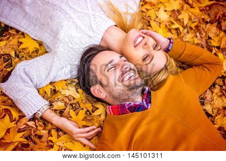 Outdoors portrait of a happy young couple.Beautiful couple lying in the park among leaves and smiling.They are enjoying in the beautiful autumn day.