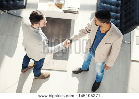 Handshake between two business executives.Image of two successful business partners working at meeting in office.They are working on a new project.