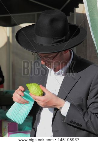 BNEI- BRAK, ISRAEL - SEPTEMBER 17, 2013: A young religious man - Jewish closely examining citrus - fruit for the holiday of Sukkot. The traditional holiday bazaar before Sukkot