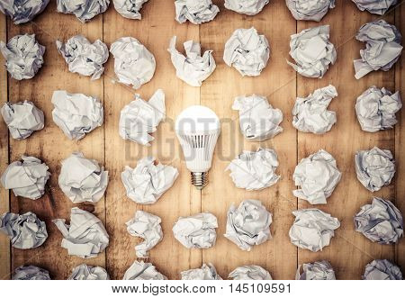 A turned on LED light bulb surrounded by crumpled paper ball / Business with new bright ideas and innovation concept