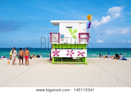 MIAMI BEACH, USA - AUGUST 6, 2016 : Young people enjoying the beach next to a colorful lifeguard tower on a sunny day in South Beach
