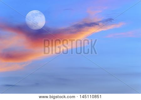 Sunset moon is a blue sky with intense vivid colorful clouds and a full moon rising in the sky.