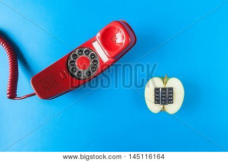 Alphanumeric apple and old red phone on a blue background