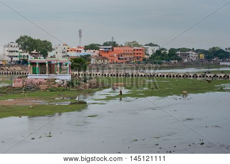 Madurai India - October 19 2013: Broad view on shallow Vaigai river with empty Meenakshi shrine and pedestrian bridge. Horses and people in the photo.