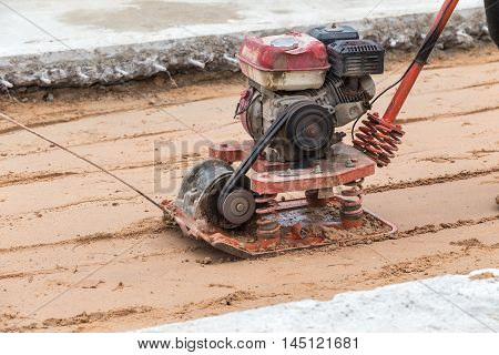 Worker With Red Soil Compactors In Construction Site