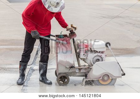 Worker Cutting Concrete Road With Diamond Saw Blade Machine