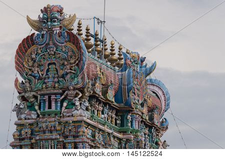 Madurai India - October 19 2013: Closeup of the top of the East Gopuram of the Meenakshi Temple against bluish white skies. Pastel colors and statues.