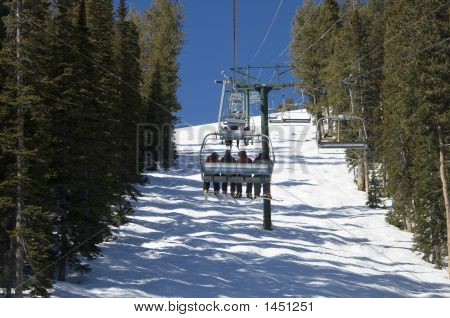 Skiers Riding Up The Chair Lift