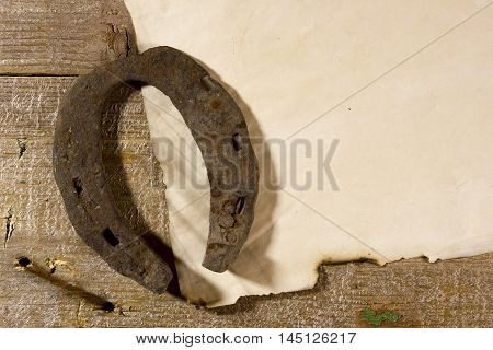 Old horseshoe and the sheet of paper on a wooden table