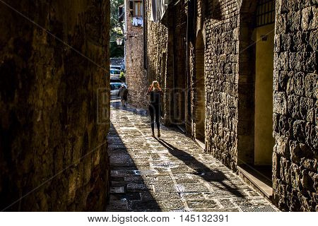 Girl walking in an alley in Italy with shadow - tuscany
