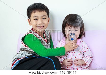 Asian child was bronchitis and crying. Kindly brother smiling and take care his sister with asthma problems making inhalation by mask at hospital. Happy family concept loving and bonding of sibling.