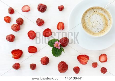 flat lay with red strawberries and frothy coffee on light wooden background top view / coffee strawberry background