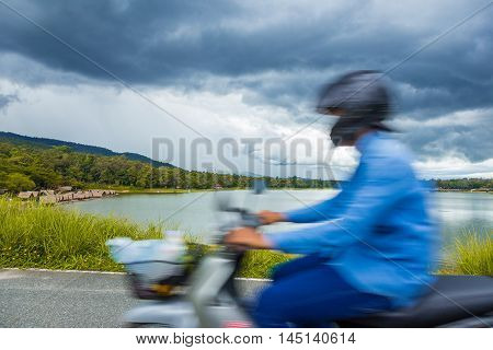 View of Huay Tung Tao Lake from across the road with distant food rafts around the lake and mountains and dark blue thunder storm clouds in the background shwing blurred person on motorcycle in the foreground passing by