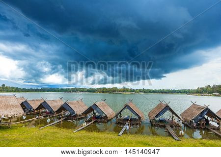 View of Huay Tung Tao Lake with food rafts around the lake and mountains and dark blue thunder storm clouds in the background
