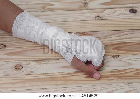 Gauze bandage the hand contusion. treating patients with  a wrist left male  wrapping his injury, On a wooden table