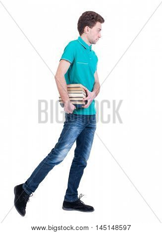 side view of going man carries a stack of books. Curly kid in a turquoise jacket goes to the side with a bundle of books.