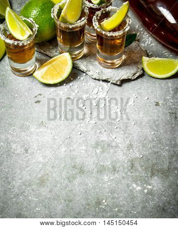 Tequila with salt and lime slices. On the stone table.