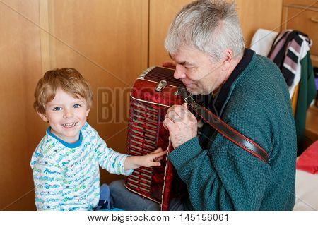Happy blond little kid boy and his grandfather playing together with accordion. Senior man teaching his grandson, cute toddler to play with music instrument at home.