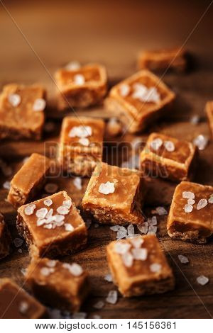 Toffees. Salted caramel pieces and sea salt close up top view. Butterscotch toffee caramel