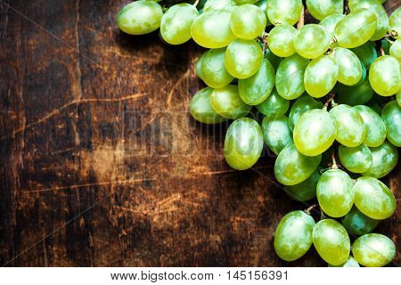 Fresh white grapes over wood table macro. Bunch of Grapes on a vintage wooden background