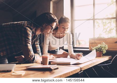 Finding solution together. Confident young man and woman in casual wear looking at blueprint together while both standing near wooden desk in creative office