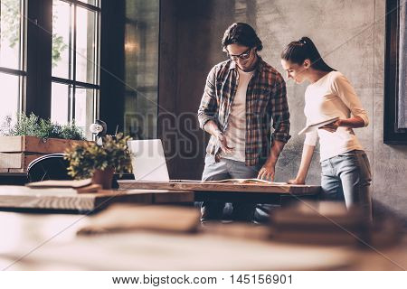 Discussing business with colleague. Confident young man and woman working together while standing near the desk in creative office