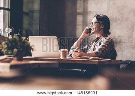 Staying in touch with his colleagues. Cheerful young man in casual wear looking through window and talking on the mobile phone while sitting near at the desk in creative office