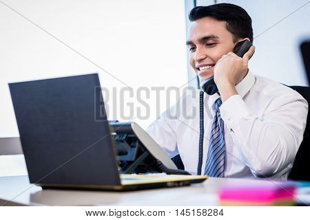 Asian salesman in office making business phone call sitting at laptop computer