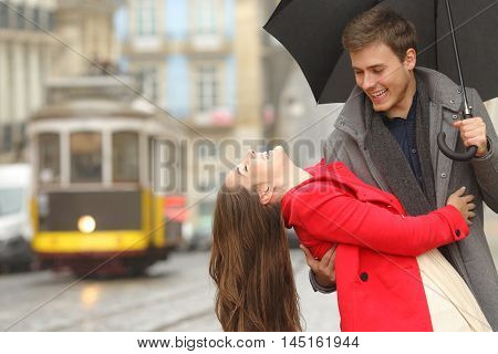 Happy playful couple in love dating joking and laughing in the street of an old town in a rainy day under an umbrella